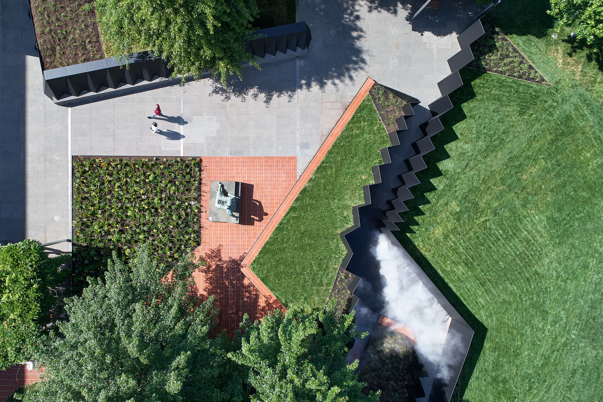 Doubleground transforms the NGV's Grollo Equiset Garden with a site-specific work of temporary architecture by literally raising sections of the landscape and creating chasm-like passageways for visitors to explore between the tilted embankments.